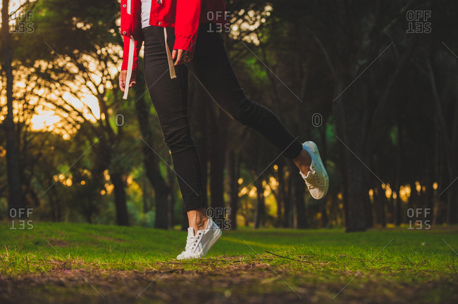 Crop shot of woman in sportive jacket and sneakers jumping slightly standing on tiptoe on green grass in park