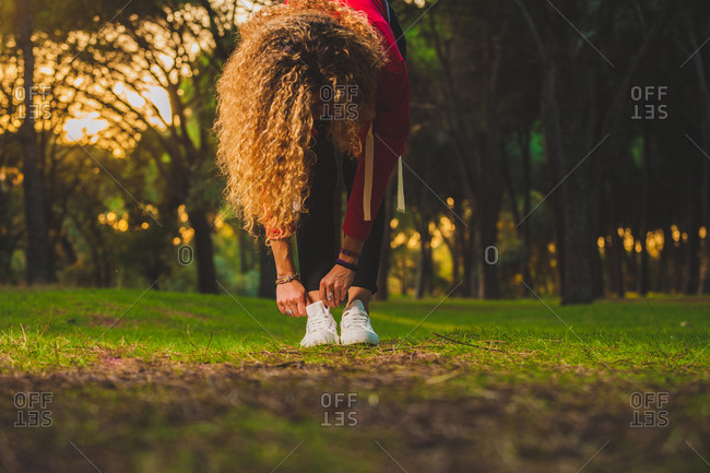 Sportive curly woman bending forward on lawn