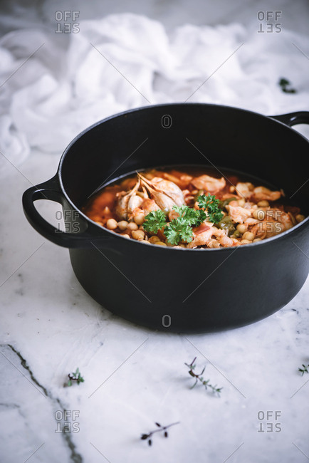 Stew pot of freshly made vigil potaje dish placed on white marble counter