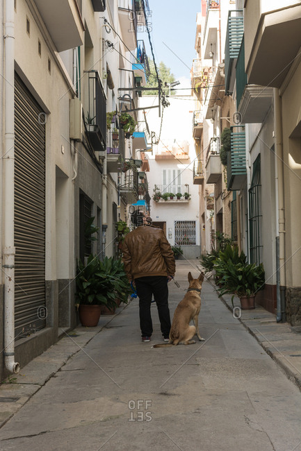 Young man walking, taking care and giving love to his dog through the streets of his town