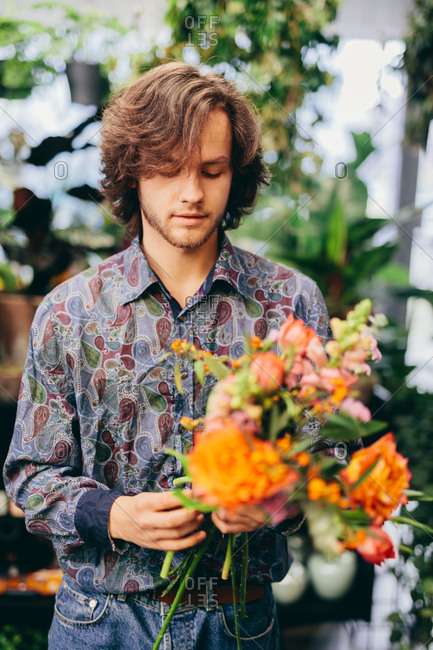 Man making a flower bouquet. Flower shop, business. Work and occupation.
