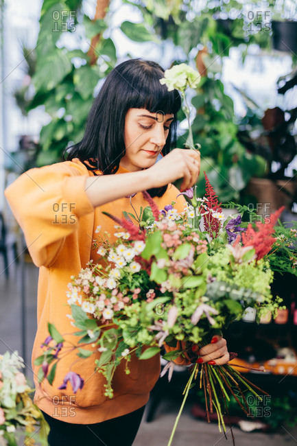Florist making a flower bouquet from colorful flowers. Flower shop, business owner. Work and occupation.