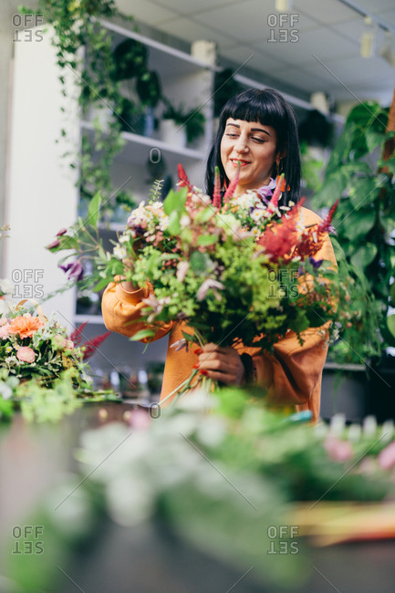 Woman making a colorful bouquet from cut flowers. Business and professional occupation.