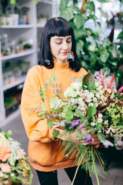 Florist composing flowers in a bouquet. Small business, retailing. Natural floral decorations.