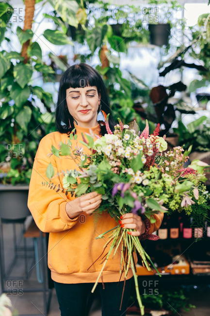 Florist holding flower bouquet in the flower shop. Work, occupation, owning a business.