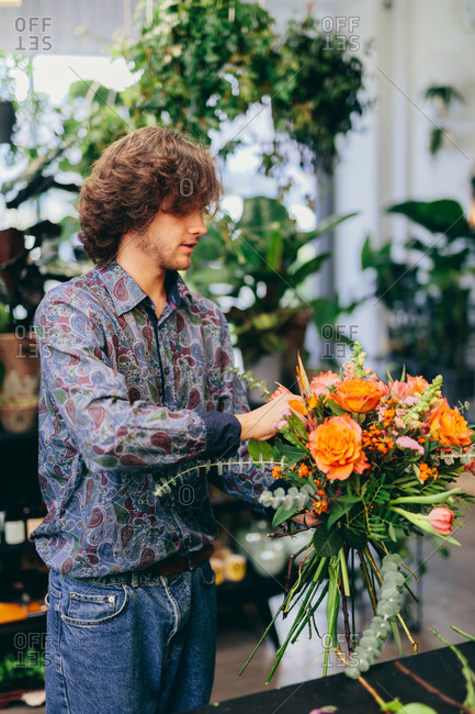 Man making a colorful flower bouquet. Florist, business and work. Natural floral decorations.