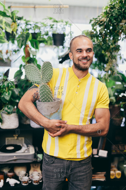 Happy man holding a cactus pot in his hands. Original houseplant, flower shop. Shopping.
