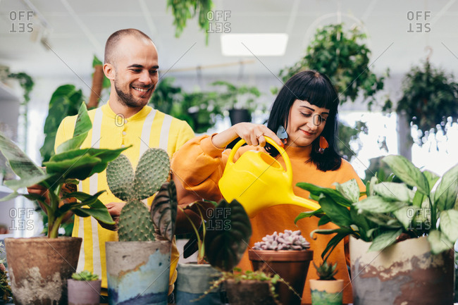 Man and woman working at the flower shop. Small business owners, professional occupation.