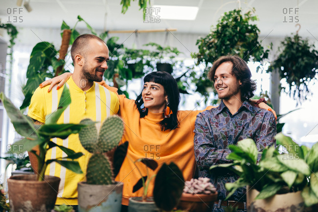 Woman and two men in the flower shop, surrounded by plants. Team, work, small business.
