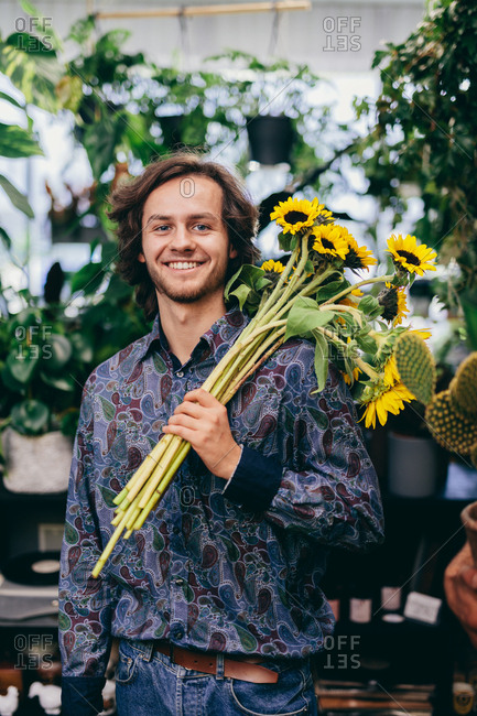 Man carrying bunch of sunflowers. Florist, flower shop, business. Work and occupation.