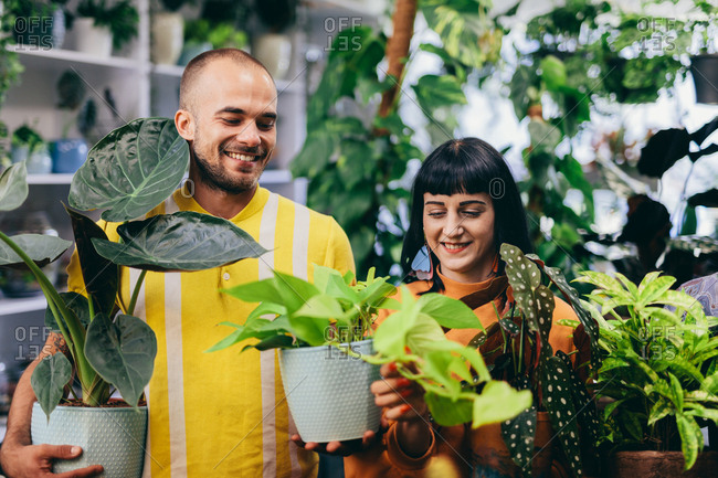 Man and woman carrying plants in pots. Flower shop, florist. Small business, teamwork.