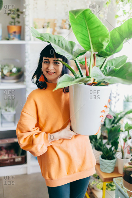 Woman holding a big plant in a pot in the flower shop. Flower shop, florist, business owner.