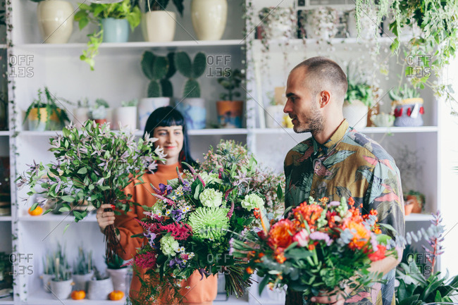Man and woman carrying bouquets in the flower shop. Florist, small business, creative work.