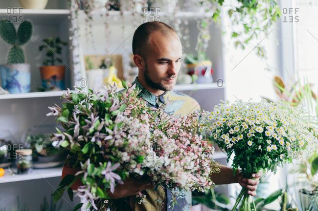 Man holding cut flowers in his hands. Flower shop, florist. Small business, creative job.