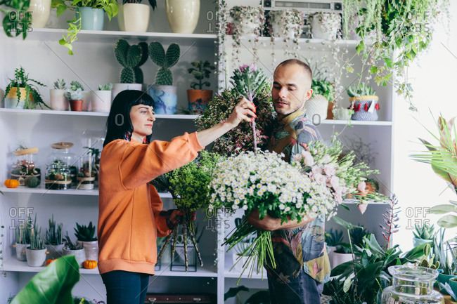 Man and woman making bouquets in the flower shop. Small business owners, creative job, retailing.
