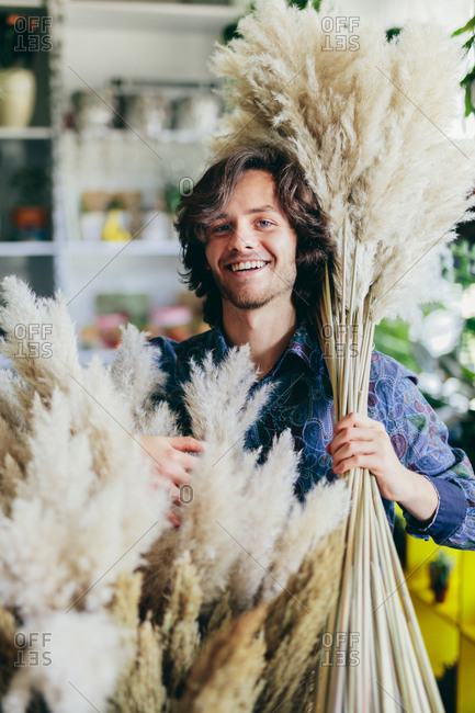 Man carrying fluffy grass in the flower shop. Small business, retailing, shopping. Creative occupation.