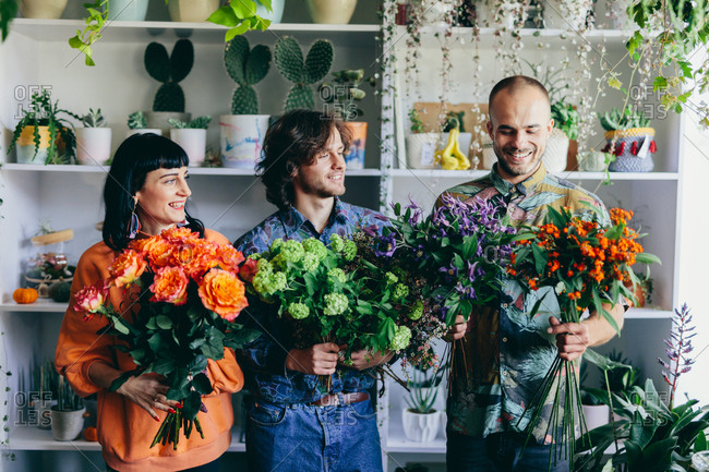 Woman and two men holding flower bouquets in the flower shop. Small business, creative occupation. Teamwork.