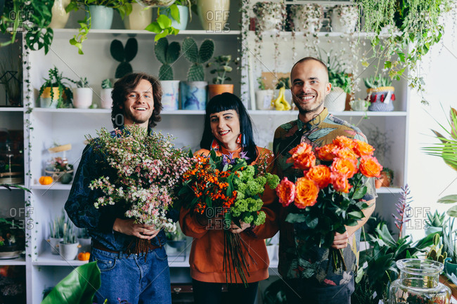 Woman and two men holding flowers in the flower shop. Small business, creative occupation. Teamwork.