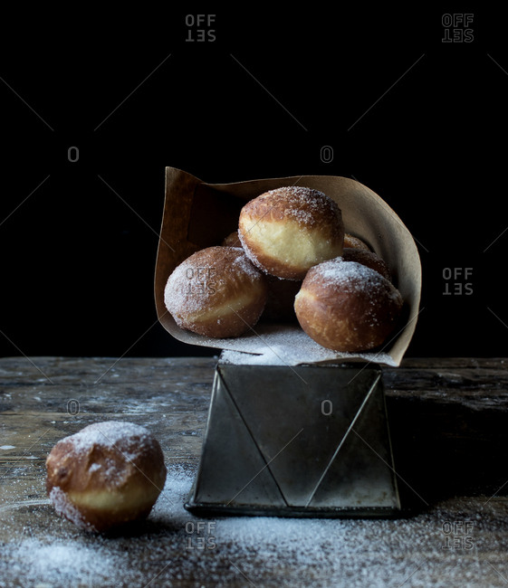 Fresh cake near set of baked loaf in craft paper with powdered sugar on wooden table in darkness on black background