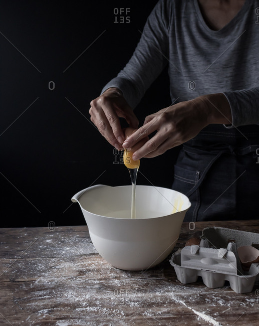 Crop human breaking egg in bowl on wooden table with flour on black background
