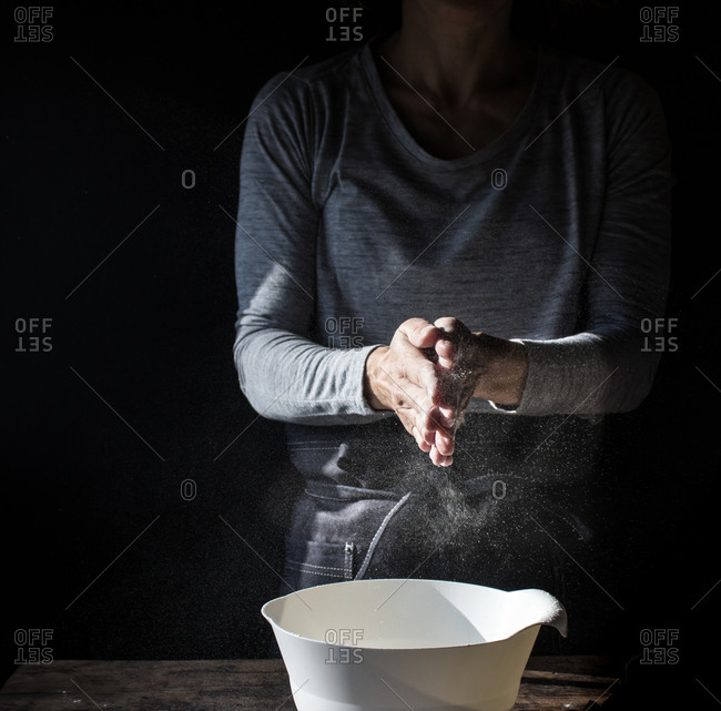 Crop lady clapping hands in flour near bowl, box of eggs and whisk on wooden table on black background