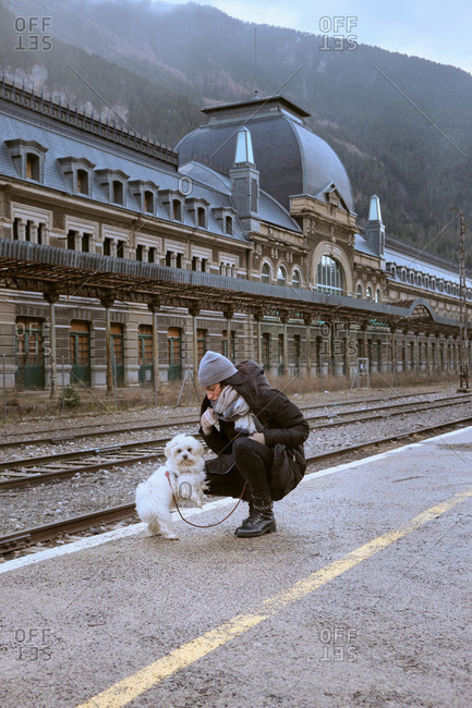 Female in warm clothes with funny white dog sitting near beautiful building on Canfranc railway station in Huesca, Spain