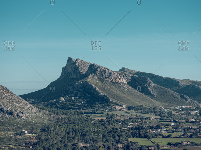 Magnificent drone view of mountain ridge and amazing city on seashore on sunny day on Mallorca, Spain