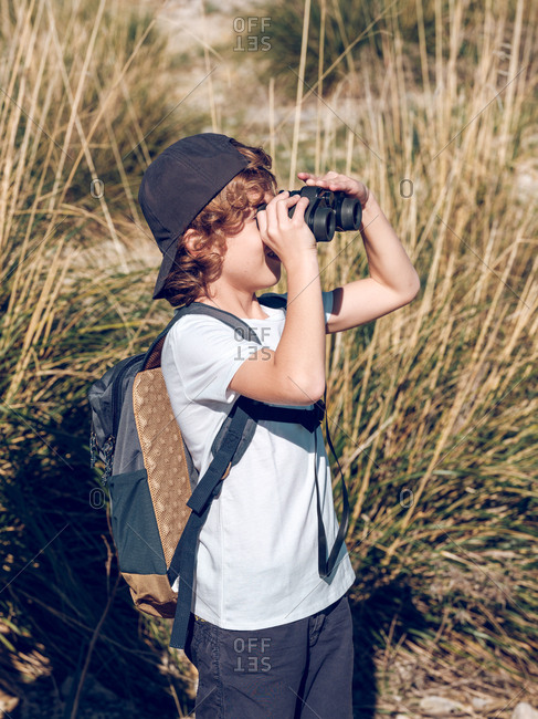 Side view of little boy with backpack looking at distance through binoculars while standing on background of tall grass in countryside