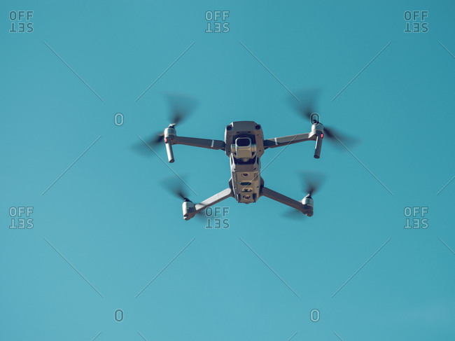 From below shot of modern drone flying in cloudless blue sky on sunny day on Mallorca, Spain