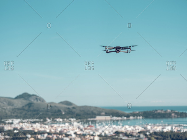 Modern drone flying towards beautiful sea against cloudless blue sky on Mallorca, Spain