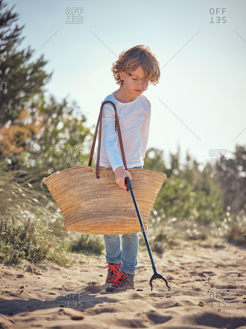 Child with container on shoulder and litter picker cleaning up garbage from ground on field