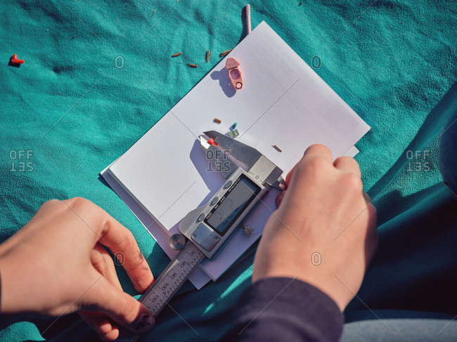 From above crop hands of persons gauging by vernier caliper little plastic things on paper on blue coverlet placed on ground