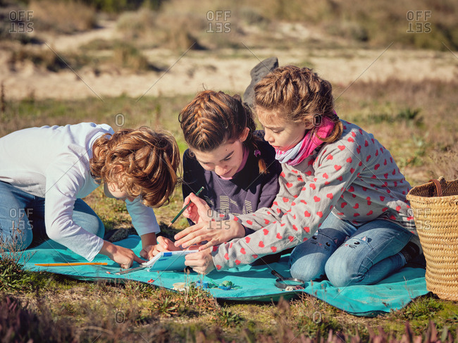 Young lady with pencil writing in notebook and children gauging by ruler little plastic things and lying on coverlet on ground