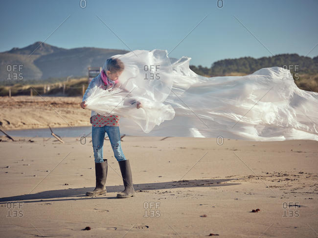 Concept of child entangled in white textile waving by wind on sand coast on mountain background