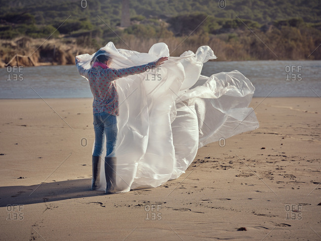 Back view of child with hands to sides entangled in white textile waving by wind on sand shore