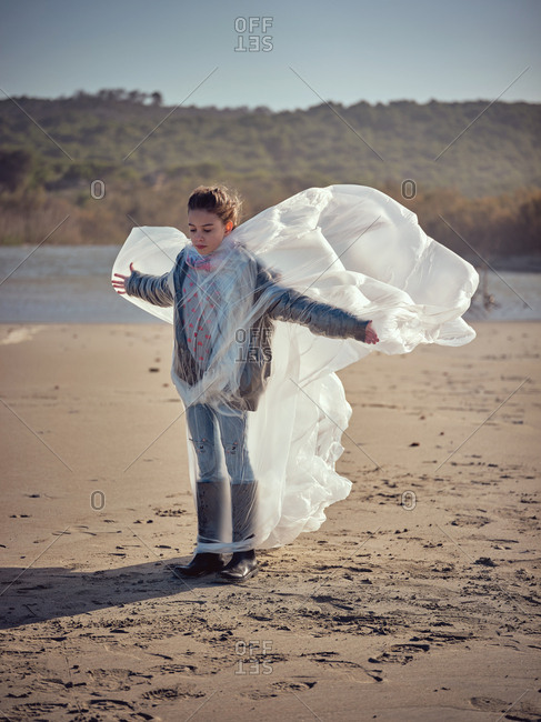 Girl entangled in plastic on river coast