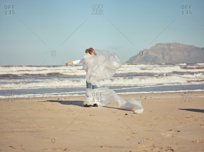 Back view of girl with hands to sides entangled in white textile waving by wind on sand shore near water on mountain background