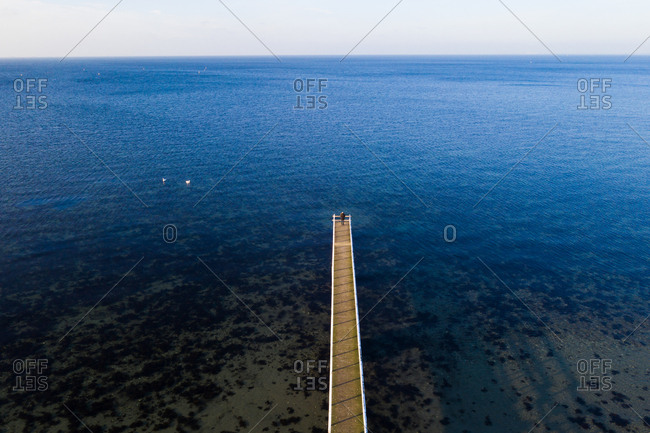Elevated view of person standing at end of a long pier