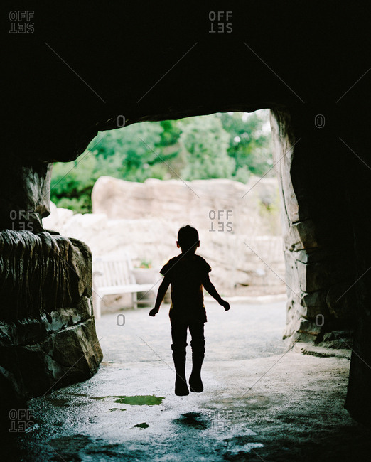 Silhouette of child jumping in a cave