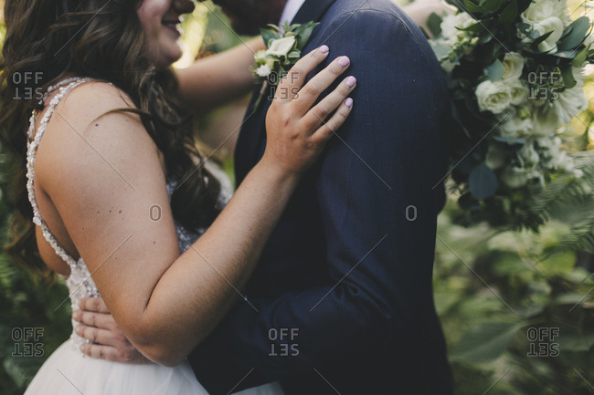 Bride and groom embraced outdoors