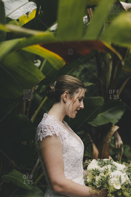 Profile of bride holding bouquet surrounded by tropical plants