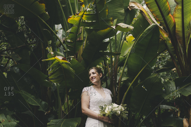 Beautiful bride holding bouquet surrounded by tropical plants