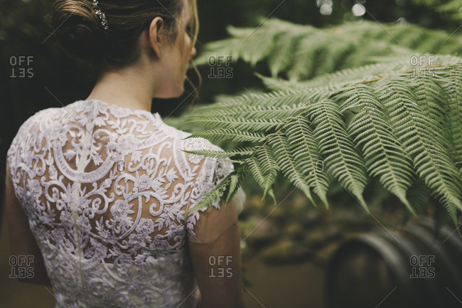 Rear view of bride walking by green foliage