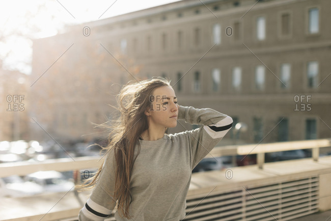 Young woman with long hair blowing in wind while walking in a city