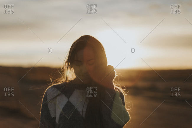 Backlit portrait of a young woman with long hair at sunset