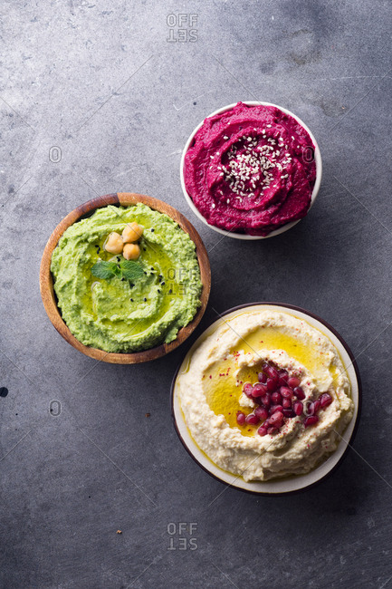 Creamy chickpea hummus, green pea hummus and spicy roasted beetroot dip with sesame seeds