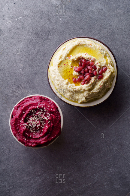 Creamy chickpea hummus and spicy roasted beetroot dip with sesame seeds