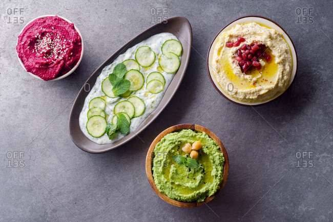 Overhead image of israeli side dishes: three types of hummus and yoghurt sauce with cucumbers, herbs and garlic
