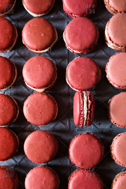 Macarons in shades of pink creating a pattern on a gray background
