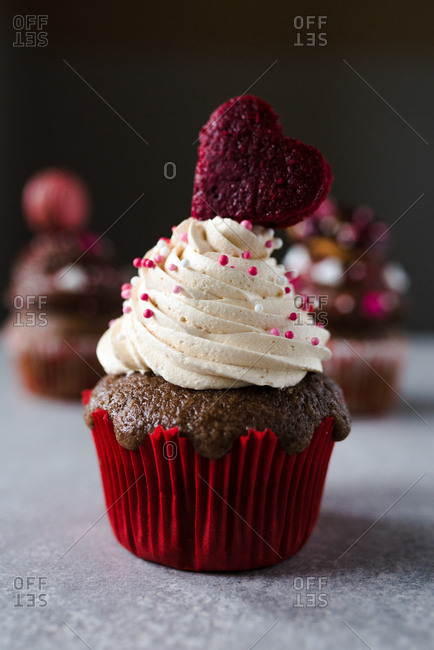 Valentine's day themed cupcake with white cream and heart as decoration